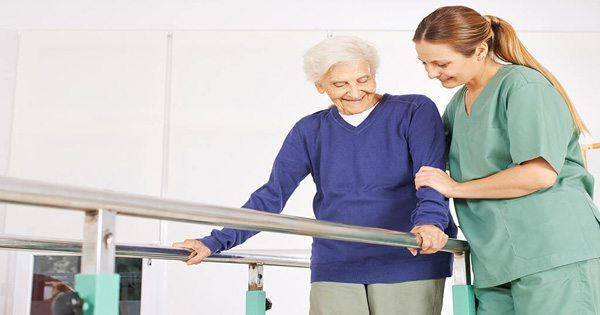 blog picture of elderly woman being helped by physical therapist nurse