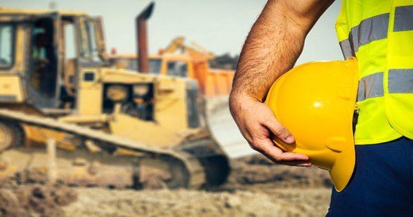 Imagen de blog del fondo del sitio de construcción de la mano del trabajador sosteniendo su casco