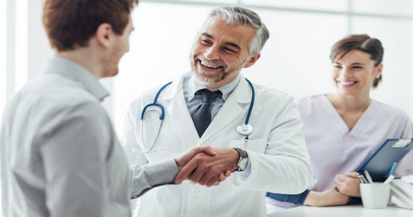 blog picture of doctor shaking patients hand with nurse or assistant in background