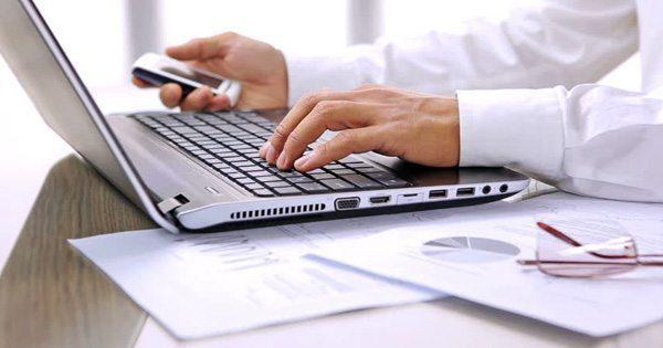 Imagen de blog del teclado de la computadora portátil y la mano izquierda de un hombre en las teclas y la mano derecha sosteniendo el teléfono celular