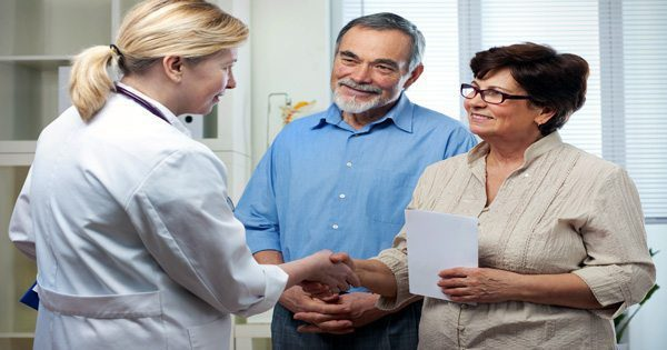 blog picture of doctor talking with an older couple about chiropractic