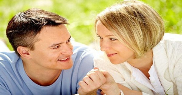 blog picture of couple laying in the grass holding hands smiling at each other