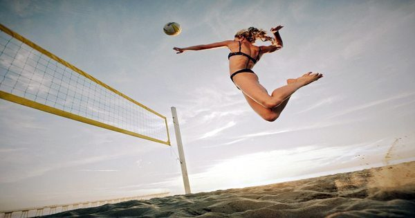 blog picture of a lady playing beach volleyball jumping high for a spike