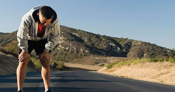 blog picture of runner catching his breath while running on the road around hills