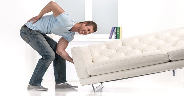 blog picture of man lifting couch and grabbing his back in pain