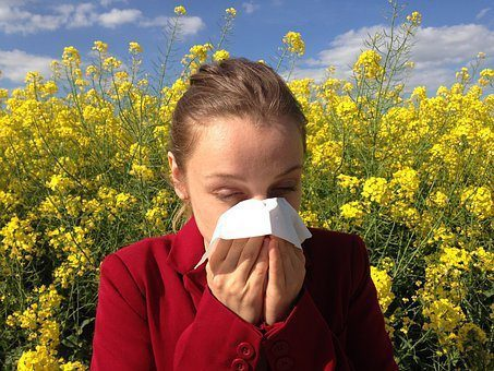 blog picture of lady in flower field with allergies