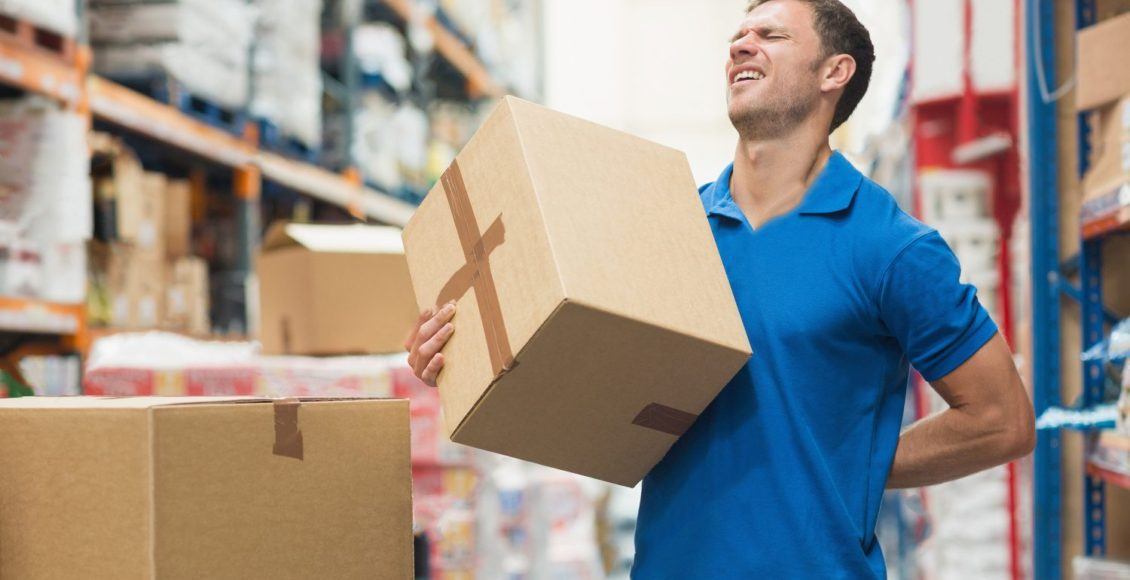 Trabajador con dolor de espalda mientras levanta la caja en el almacén