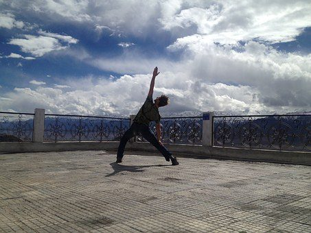 blog picture of man stretching on a building roof