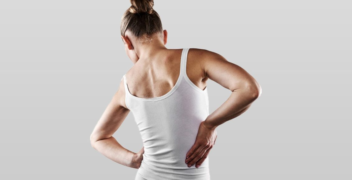 young female in white shirt suffering from backache scoliosis
