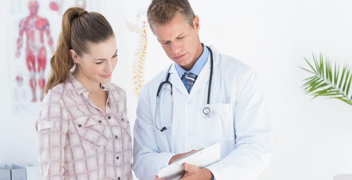 Chiropractor muestra la información del portapapeles del paciente