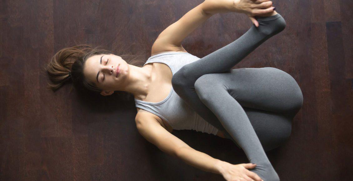 modelo joven que se resuelve en casa haciendo ejercicio de yoga en el suelo en supta