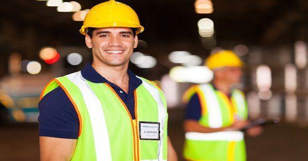 Trabajador de la construcción sonriendo con antecedentes de otros trabajadores