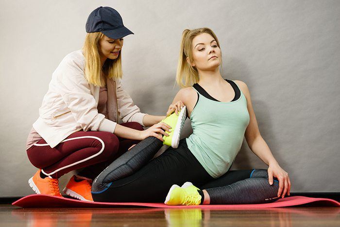 Lady helps another lady stretch