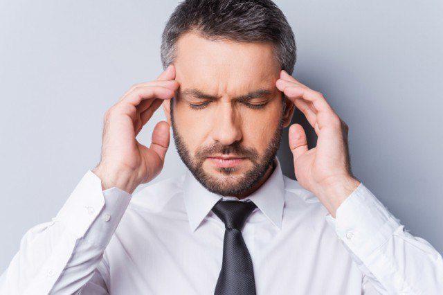 El hombre sostiene su cabeza con ambas manos siguiendo los síntomas después de lesiones automotrices.