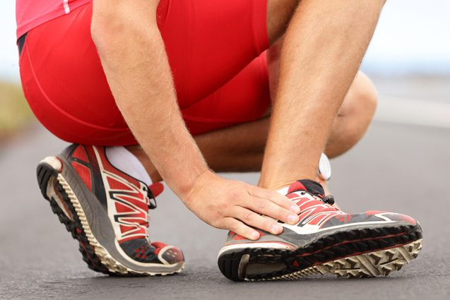 Male athlete massages his foot due to ankle pain.