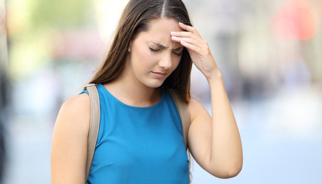 Woman holding her head as she feels symptoms of vertigo.
